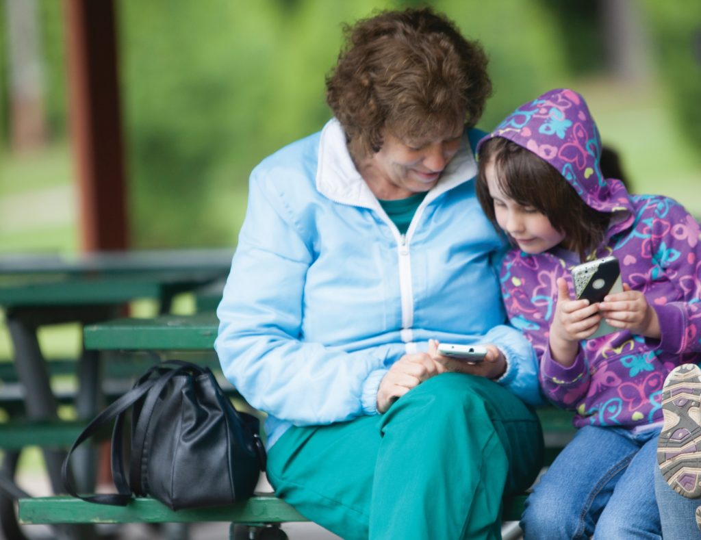 Young girl leans in close to older woman, looking at a phone.