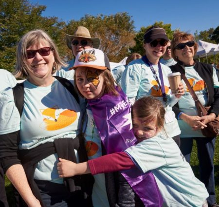 A family in matching t-shirts group-hugs at the Rise Above Seizures walk.