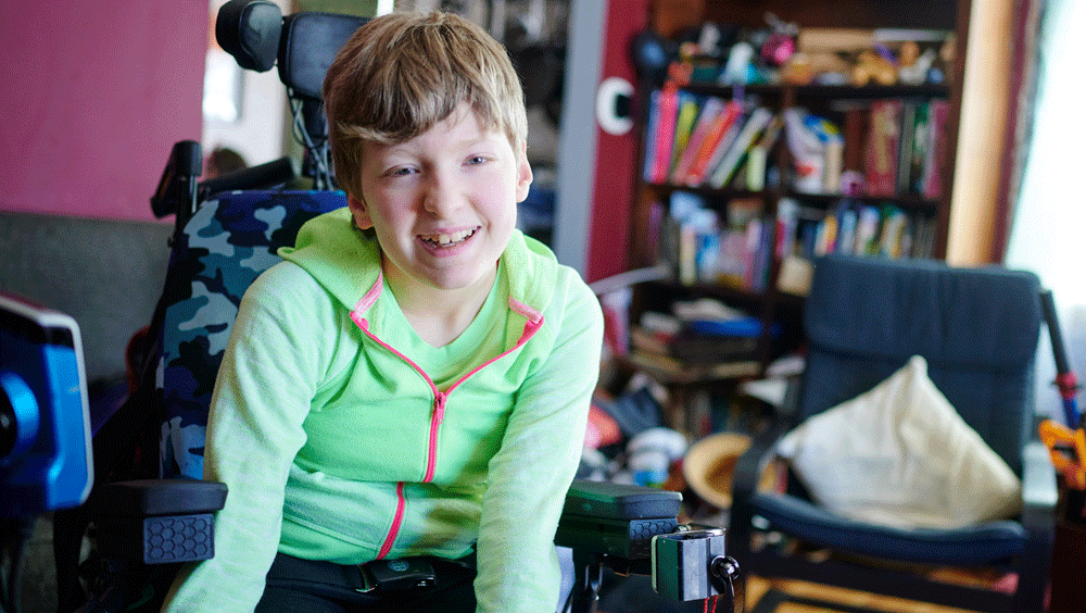 A young girl in bright green leans forward in her wheel chair, smiling