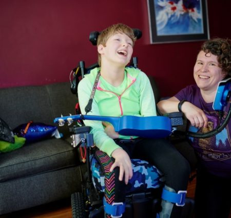 A girl in bright green sits in her wheelchair and laughs. Next to her a woman in purple kneels and smiles at the camera