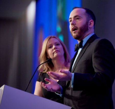 Two people wearing fancy clothes give a speech at a podium during the Epilepsy Foundation gala.