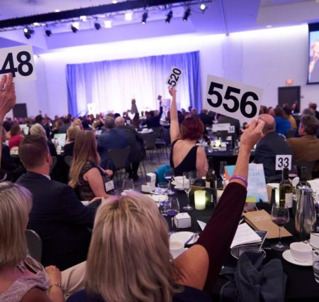 In a large crowd of people, women hold up bidder numbers for an auction.