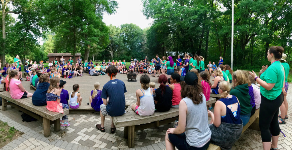 A panoramic photo shows a large group of kids and counselors gathered around a plaza at camp, sitting on wooden benches.