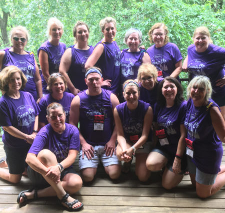 A group of adult counselors at camp pose in matching purple t-shirts that say Camp Oz.