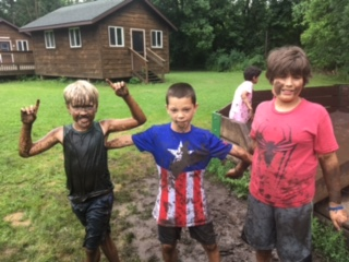 Three very muddy campers pose for a photo in front of a cabin