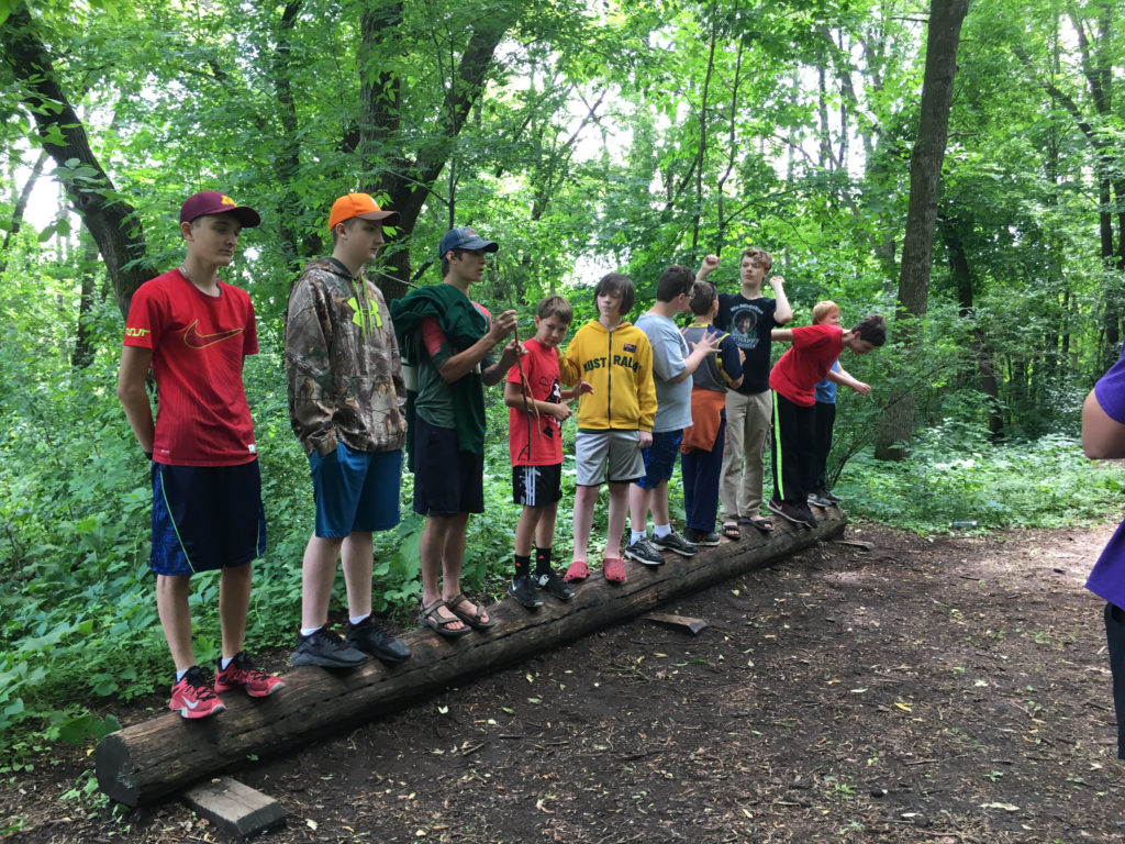 A line of boys of varied ages stands on a log in a wooded area.