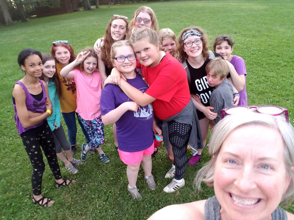 A woman takes a selfie with a large group of young girls at camp, many of them laughing and hugging.