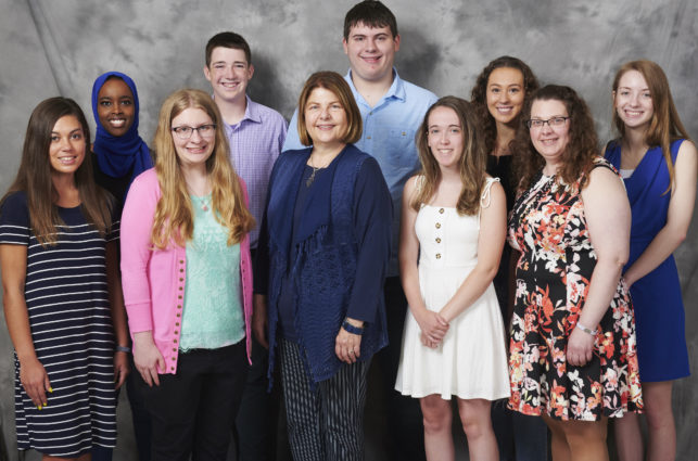 Nine college students posing with scholarship fund donor