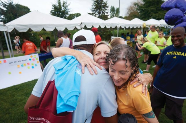 Woman wraps two friends in a big hug at an outdoor event.
