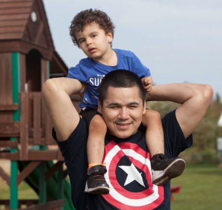 A young child with epilepsy sits on his father's shoulders in front of a playground.