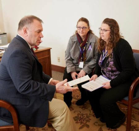 Two women sit and talk with a legislator in his office, each holding pages of information.