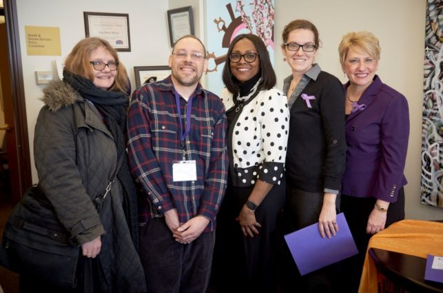 A group of people pose after an advocacy meeting with a legislator. Two of them wear purple ribbons to show their support for the epilepsy community.