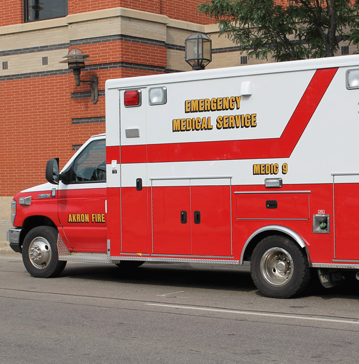 A large red and white ambulance parked in front of a medical facility.