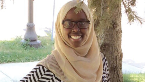 A young woman wearing a hijab and glasses smiled at the camera by a tree