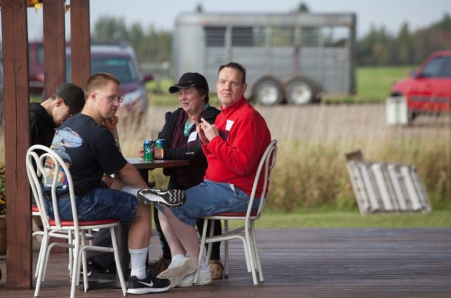 A group of people sit at a table in a park shelter on a summer day. A man in a red sweater is turned in his chair, looking at the camera.