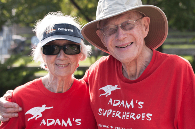 "An older couple, wearing matching t-shirts that say ""Adam's Superheroes,"" smile with their arms around each other."