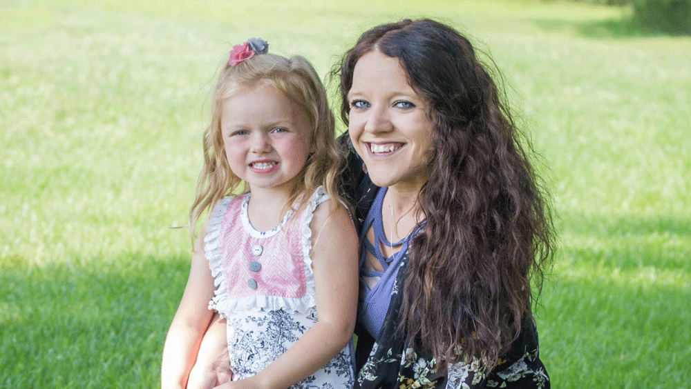 A woman with long curly hair and a young girl on her lap both smile at the camera.