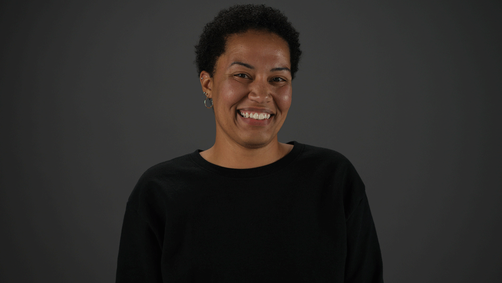 Portrait of a woman with short hair smiling at the camera against a dark backdrop.