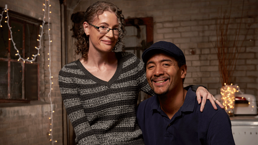 A woman sits on a man's lap in a festive room with exposed brick; both smile at the camera