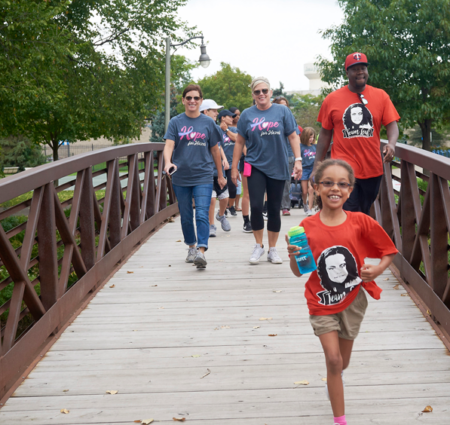 A group of people walk over a wooden bridge during the fundraising walk. A small girl runs ahead, smiling and holding a water bottle.