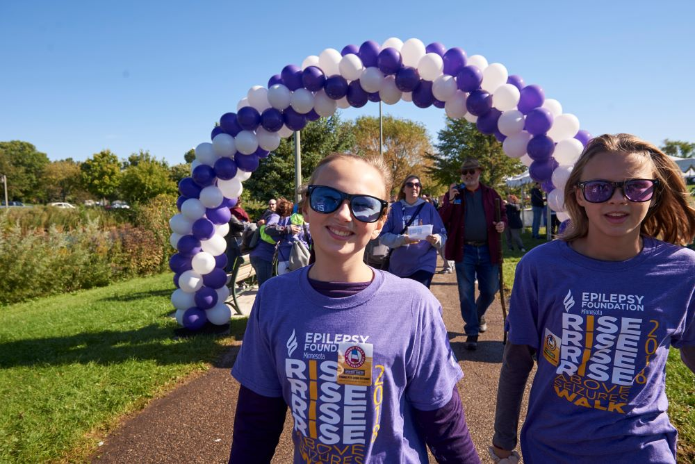 Two girls wearing Epilepsy Foundation t-shirts smile in front of an archway made of balloons.