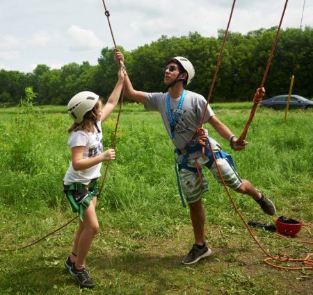 An adult and a child, both wearing helmets, work on a ropes course at camp.