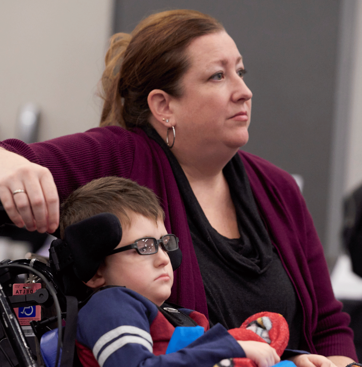 A woman in a maroon sweater leans an arm over her young son's wheelchair, listening intently to someone off camera.