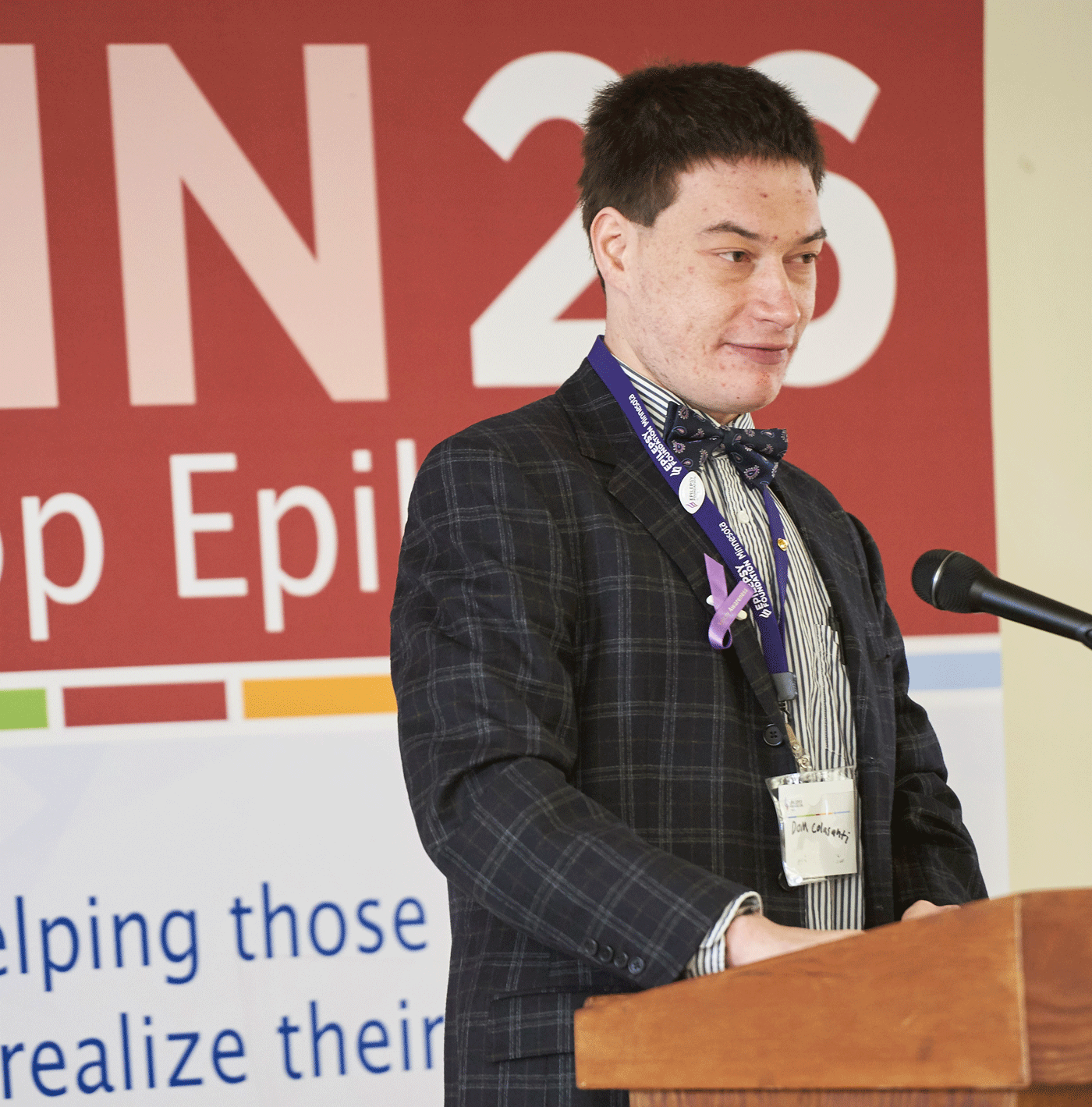 A young man with black hair and a black blazer adorned with purple ribbons stands at a podium to seppech