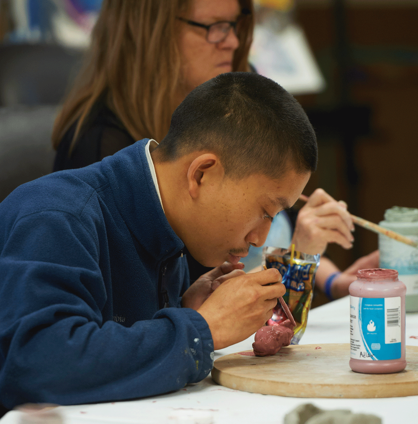 A person works on an art project, leaning in with concentration.