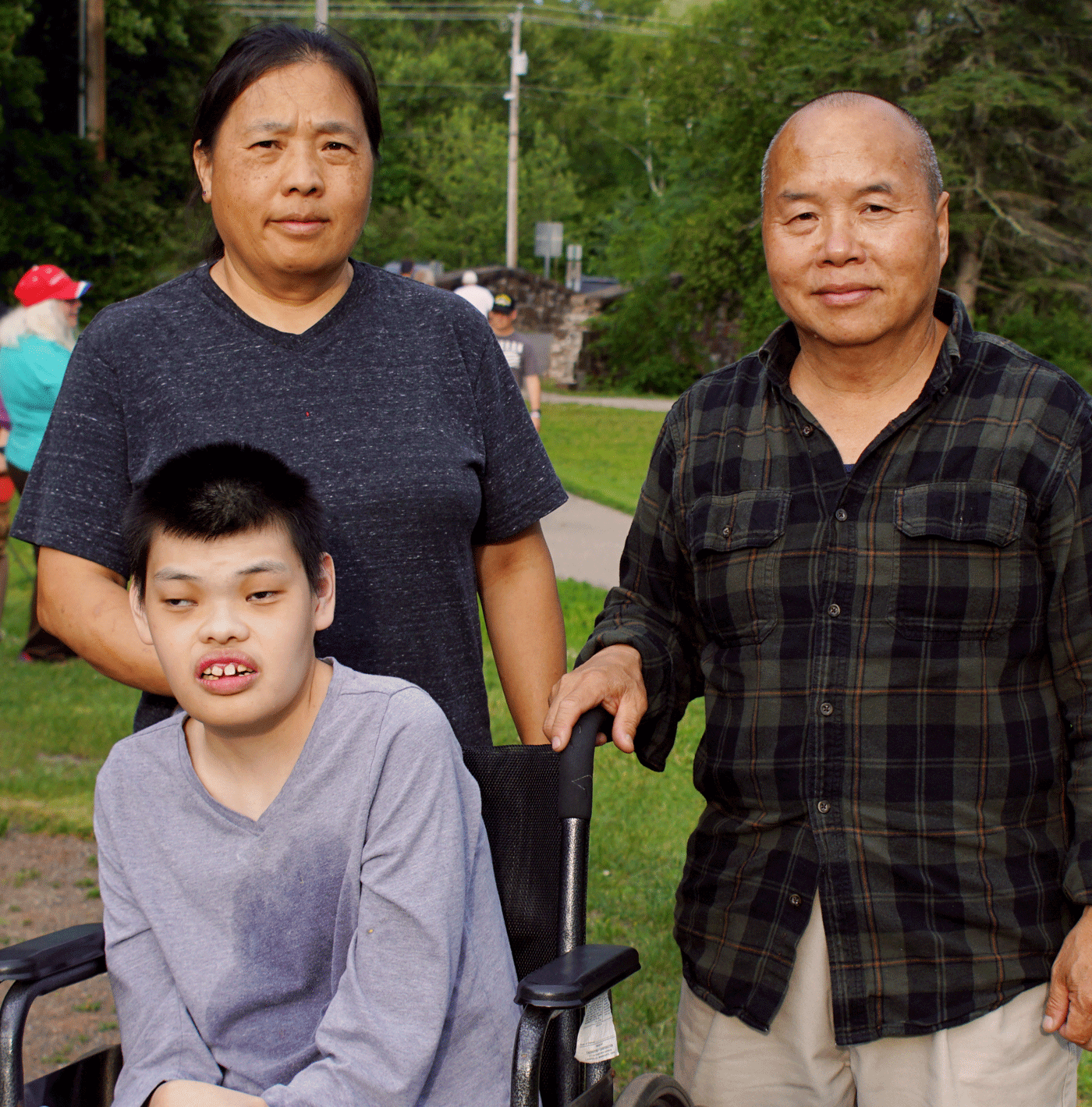 Two older people pose with a younger person in a wheelchair.