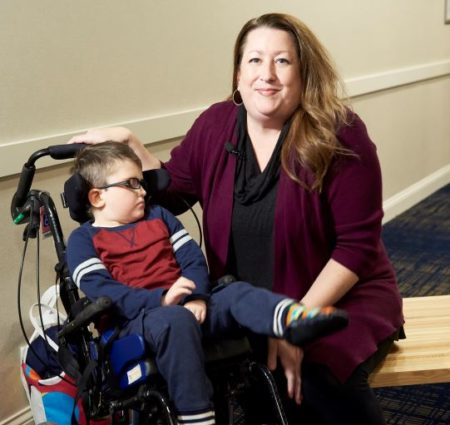 A woman wearing a maroon sweater kneels by her son's wheelchair and gives and interview to a news reporter.