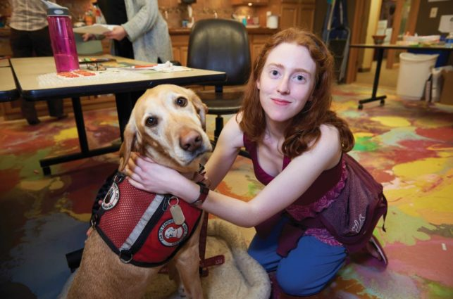 "A young woman with red hair smiles at the camera while hugging her seizure dog, a yellow lab wearing a red ""Can Do Canine"" working vest"
