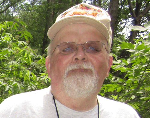 A man with a white beard and a baseball camp poses for the camera in front of camp greenery