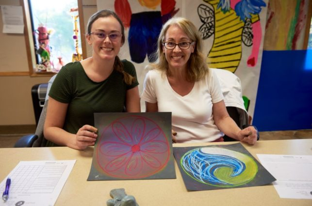 Two women smile for the camera and show off their artwork.