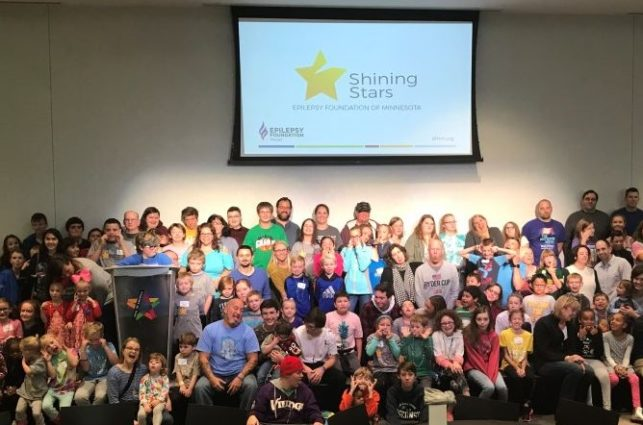 A large group of children with epilepsy and their families, in front of a screen showing the Shining Stars logo.