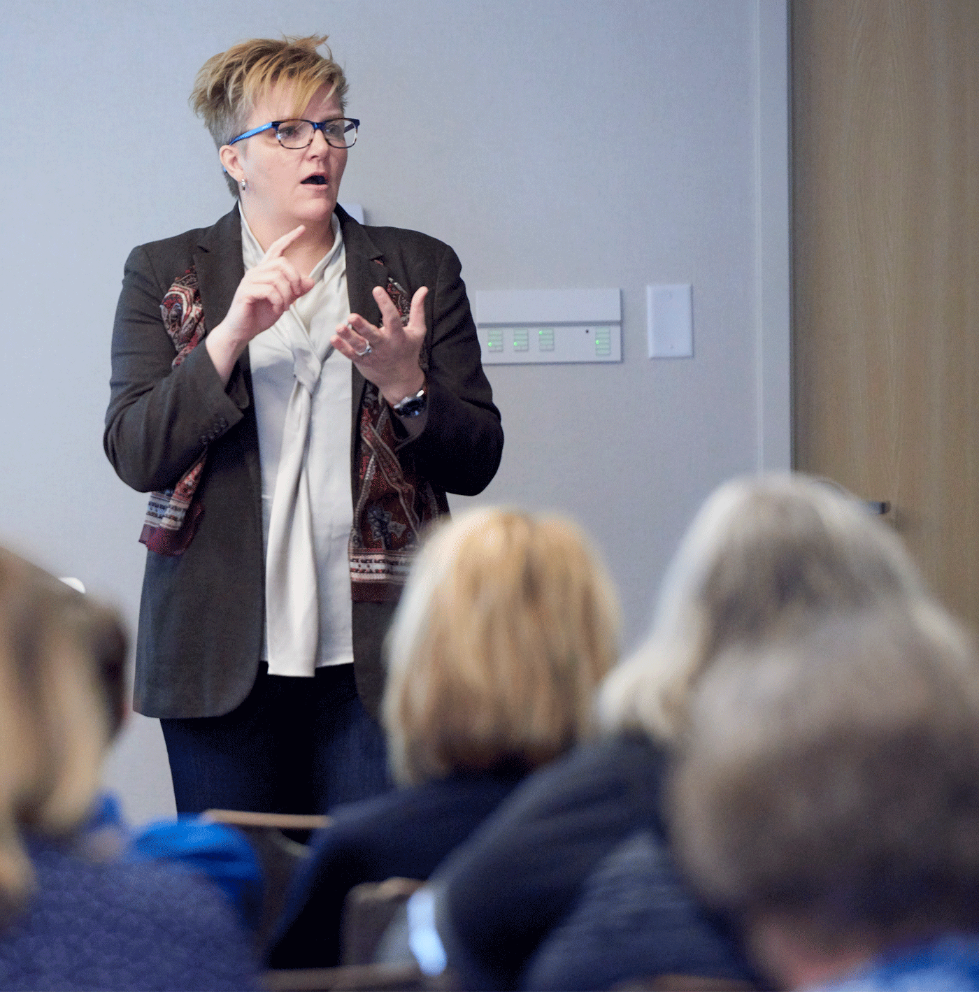 A woman with short blond hair and a black blazer counts off items on her fingers while giving a talk in front of a crowd of adults.