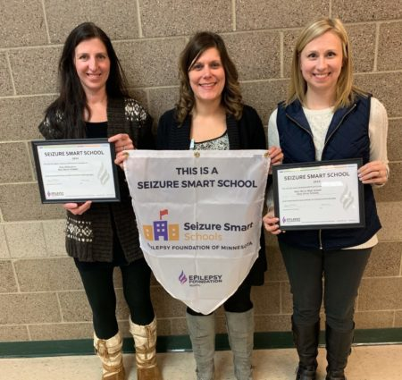 Three women stand against a wall, displaying certificates and banners showing their school is a Seizure Smart School.