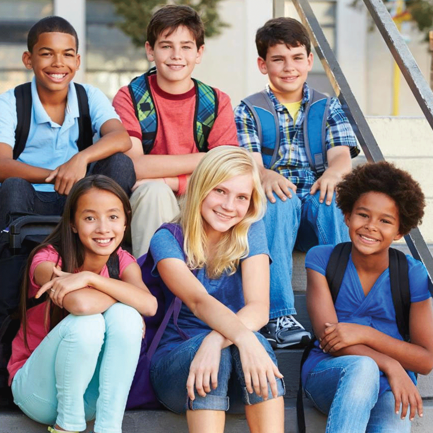 A group of students wearing backpacks sits on a flight of steps, smiling for the camera.