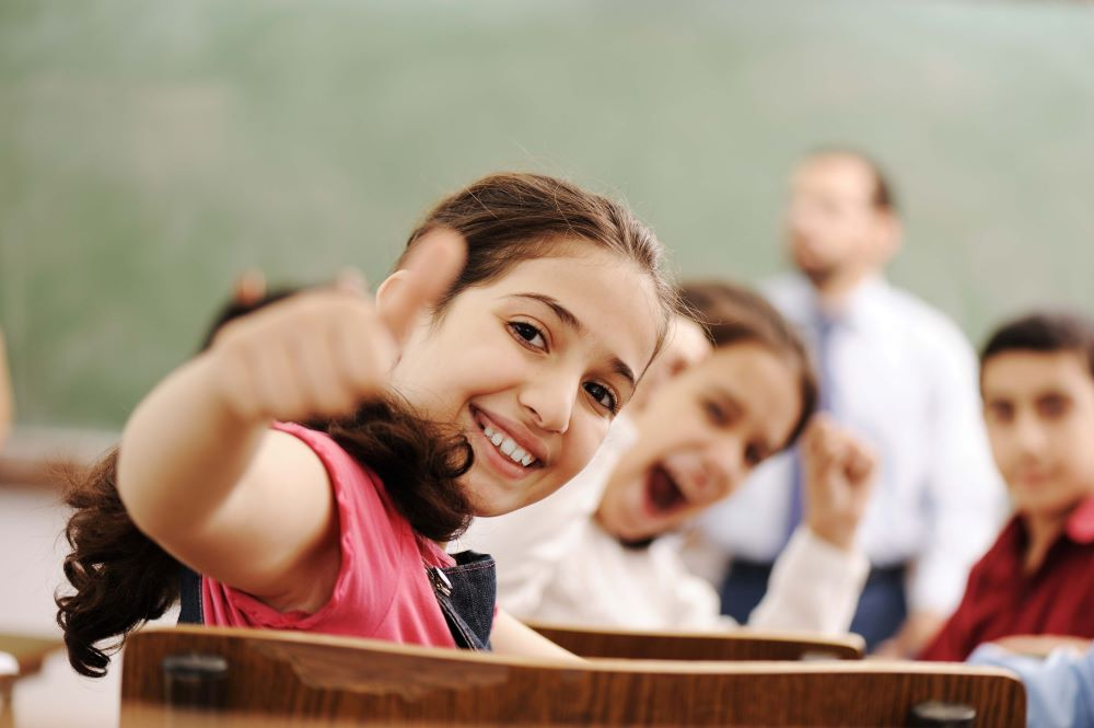 A girl gives a big smile and thumbs up to the camera. Behind her, more students smile and cheer, and a teacher stands at the front of the classroom.