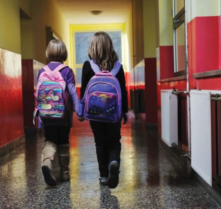 Two young students with pink and purple backpacks walk down a hallway, holding hands, their backs to the camera.