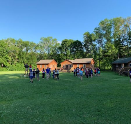 A large group of campers gather in a field in front of cabins at Camp Oz