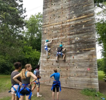 Several campers scale a climbing wall in harnesses while other campers look on
