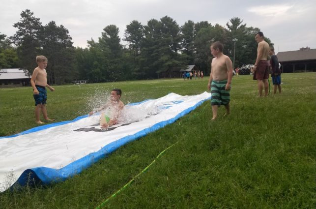 Campers in bathing suits take turns on a slip-and-slide at camp oz