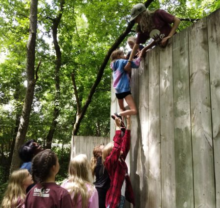Campers help each other scale a wood wall in a team-building activity