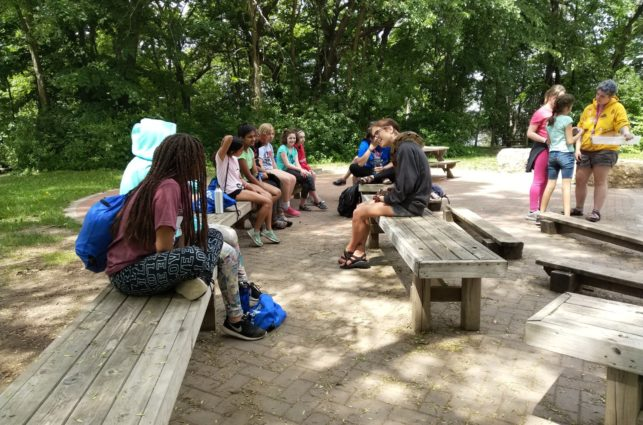 Campers sit together on wooden benches