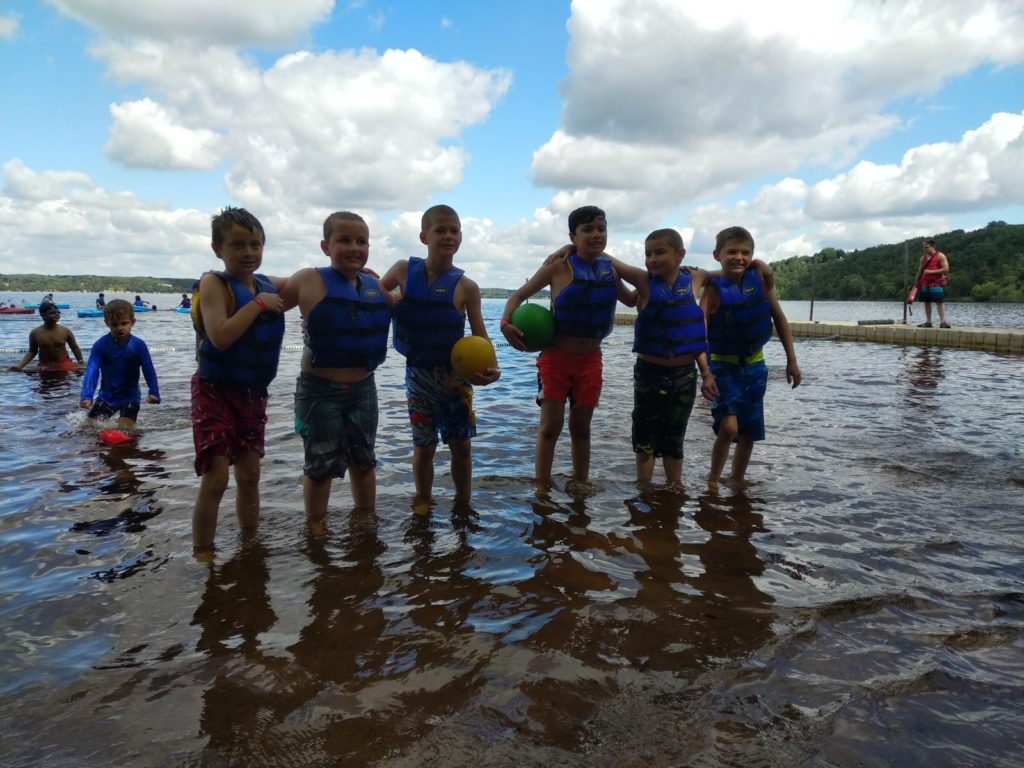 A group of campers in life preservers stand in ankle deep water