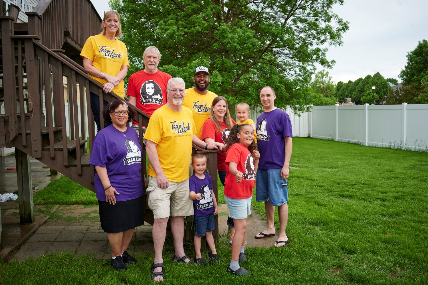 A family wearing brightly colored shirts groups together in their backyard for a team photo
