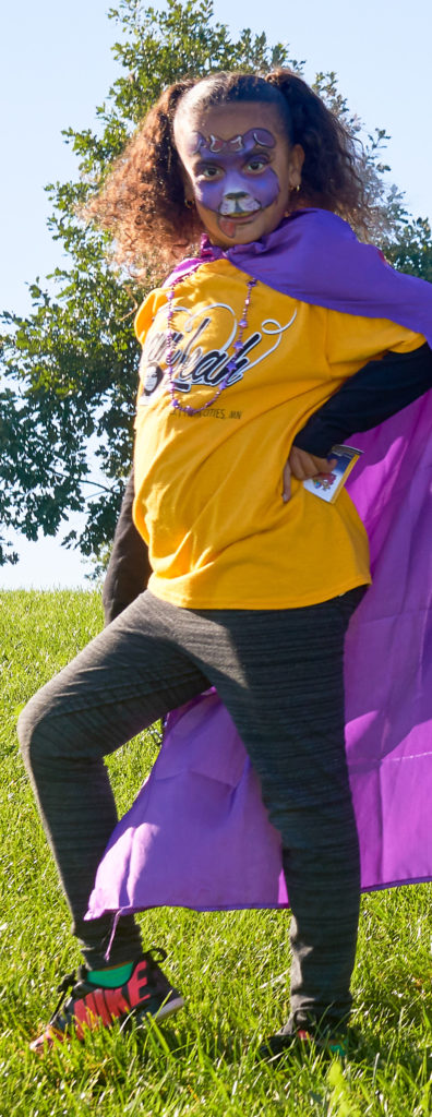 A child in a purple superhero cape and facepaint poses for the camera at the Rise Above Seizures walk