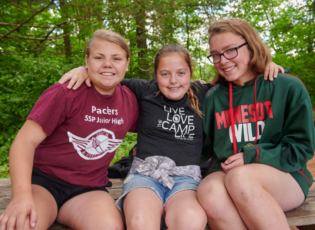 Three girl campers smiling with trees in the background