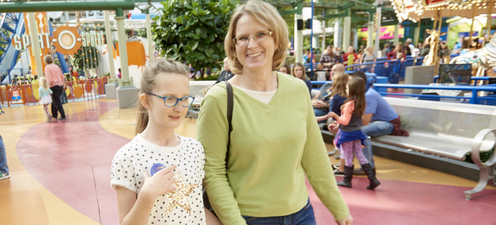 Mom holding hands with 10 year old daughter at theme park